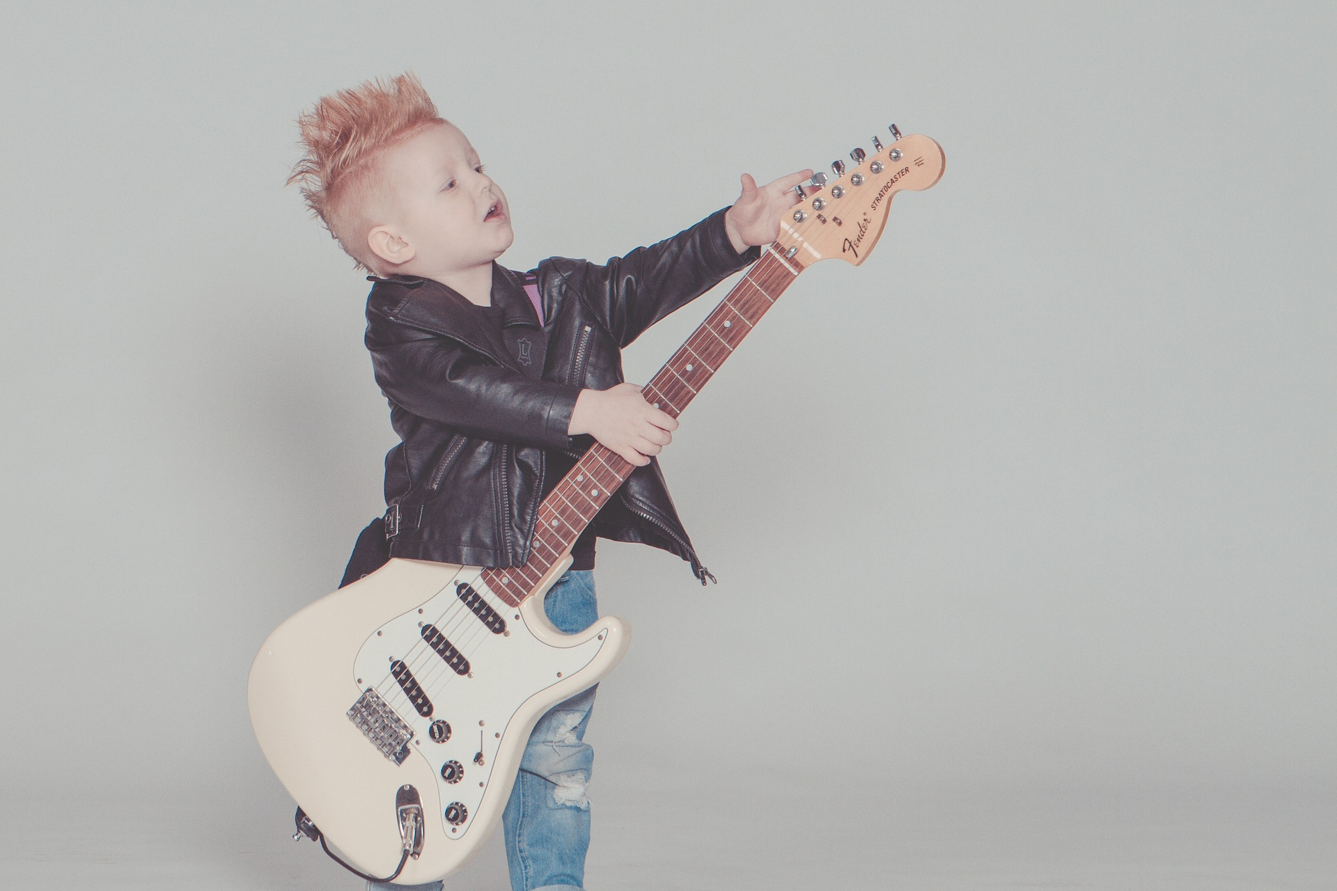 Child in leather jacket with a rock guitar. Learning through music can be a brilliant way to learn at Treforys tiny tots day childcare in Swansea